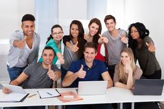 College students gesturing thumbs up sign together. Group portrait of multiethnic college students gesturing thumbs up sign together in classroom Royalty Free Stock Photo