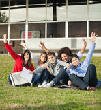 College Students With Hands Raised Sitting At Royalty Free Stock Photography