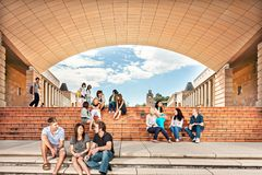 College students having chats on the floor beside buildings. University students having chats on the floor, stairs beside buildings royalty free stock photos