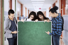College students hold empty chalkboard Stock Photo