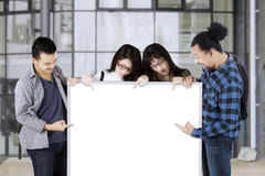 College students hold empty whiteboard Stock Photography