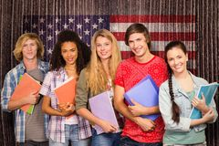 Composite image of college students holding books in library. College students holding books in library against composite image of usa national flag Royalty Free Stock Images