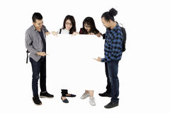 College students holding empty board. While pointing at copy space together, isolated on white background Royalty Free Stock Images