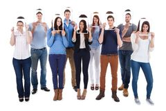 College students holding photographs in front of faces Royalty Free Stock Images