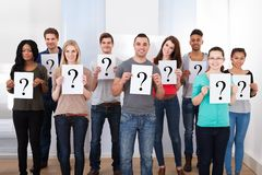 College students holding question mark signs Stock Photos