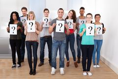College students holding question mark signs. Group portrait of confident college students holding question mark signs in classroom Royalty Free Stock Photography