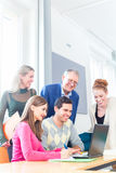 College students lerning with professor. University college students with professor in seminar using laptop for project team work royalty free stock photos