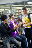 College students with music players in library. Three university students looking at music players in school library stock photos