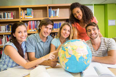College students pointing at globe in library Stock Photos