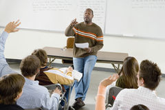 College Students And Professor In Classroom. Professor pointing at college student with hands raised in classroom royalty free stock images