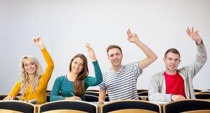College students raising hands in the classroom Royalty Free Stock Image