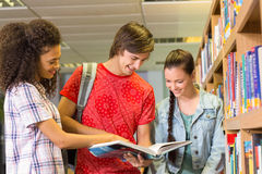 College students reading book in library Royalty Free Stock Photo