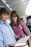 College Students Reading Book Together. Young colleges students reading book with classmates and professor in background Royalty Free Stock Images