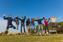 College Students on Relax. Group of Happy College Students Jumping at Park Royalty Free Stock Photo