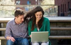 College students relaxing and looking at laptop outdoors Royalty Free Stock Image