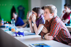 College students sitting in a classroom during class. (shallow DOF; color toned image Stock Images