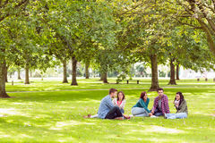 College students sitting on grass in park. Group of young college students sitting on grass in the park Stock Photo