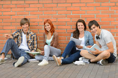 College students sitting ground by brick wall Stock Photography