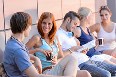 College students sitting by modern wall outside Royalty Free Stock Images