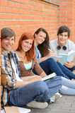 College students sitting outside by brick wall Royalty Free Stock Images