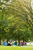 College students sitting in park Royalty Free Stock Photo