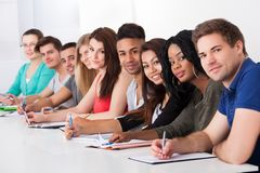 College students sitting in a row at desk Royalty Free Stock Images