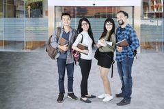 College students standing in the university. Group of confident college students standing in the university and smiling at the camera Stock Image