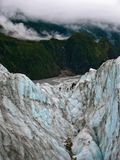 A group of tourists hike up Fox Glacier, New Zealand royalty free stock photo