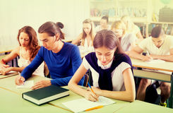 College students studying in auditorium. Group of students at their desks writing dictation in auditorium royalty free stock image