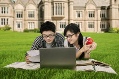 College students studying at the park. Photo of two attractive college students studying at the park while lying on the grass with books and laptop computer Stock Photography