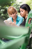 College students studying on textbook in park Stock Photos