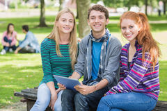 College students with tablet PC in park Royalty Free Stock Photography