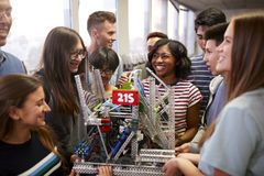 College Students With Teacher Holding Machine In Science Or Robotics Class stock photos