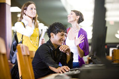 College students using computer in library. Male college student using computer and conversing with two pretty female students Royalty Free Stock Photography
