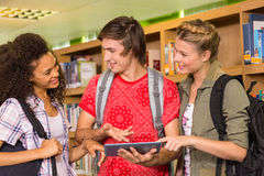 College students using digital tablet in library Stock Photo