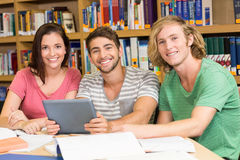 College students using digital tablet in library Stock Image