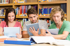 College students using digital tablets in library Royalty Free Stock Photo