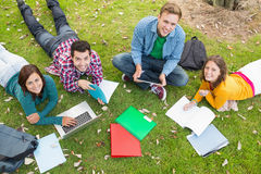 College students using laptop while doing homework in park. High angle portrait of young college students using laptop while doing homework in the park Royalty Free Stock Photo