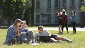College students using laptop and tablet on lawn stock video