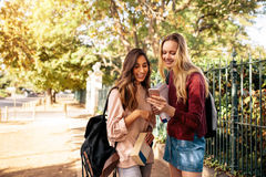 College students using mobile phone outdoors on road. Beautiful college students looking at pictures on mobile phone. Young women with book looking at smart Stock Photo