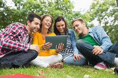College students using tablet PC in park Royalty Free Stock Photo