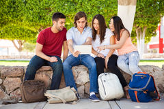 College students using technology. Group of Latin college students looking at something online on a tablet computer at school Royalty Free Stock Images