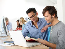 College students working with book and laptop Royalty Free Stock Photo
