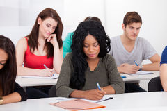 College Students Writing At Desk Royalty Free Stock Image