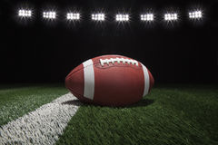 College style football on field with stripe under stadium lights Royalty Free Stock Photo
