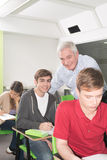 College teacher helps his students Stock Photo
