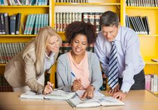 College Teachers Assisting Student With Studies In. Mature college teachers assisting student with studies in library Stock Photo