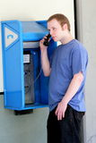 College Teenager Standing at a Pay Phone. A typical american college teenager standing making a call on a pay phone. Short hair, shallow depth of field Royalty Free Stock Photos