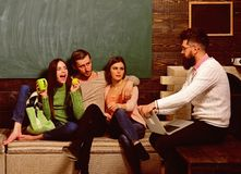 College and university concept. Students, scientists studying , professor holds laptop, teaches, explains, chalkboard stock photos