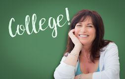 College Written On Green Chalkboard Behind Smiling Middle Aged Woman stock images